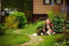 8 anos felizes da menina idosa da criança que joga com seu cão do spaniel exterior Fotos de Stock