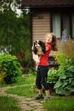 8 anos felizes da menina idosa da criança que joga com seu cão do spaniel exterior Fotografia de Stock Royalty Free