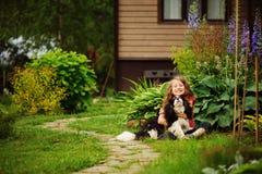 8 anos felizes da menina idosa da criança que joga com seu cão do spaniel exterior Fotos de Stock Royalty Free