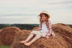 7 anos felizes da menina idosa da criança na camisa e no chapéu de manta do estilo country que relaxam no campo do verão com pilh Foto de Stock