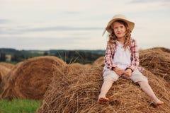 7 anos felizes da menina idosa da criança na camisa e no chapéu de manta do estilo country que relaxam no campo do verão com pilh Imagem de Stock