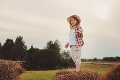 7 anos felizes da menina idosa da criança na camisa e no chapéu de manta do estilo country que relaxam no campo do verão com pilh Foto de Stock Royalty Free