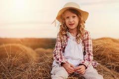 7 anos felizes da menina idosa da criança na camisa e no chapéu de manta do estilo country que relaxam no campo do verão com pilh Fotos de Stock Royalty Free