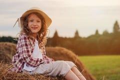 7 anos felizes da menina idosa da criança na camisa e no chapéu de manta do estilo country que relaxam no campo do verão com pilh Fotografia de Stock