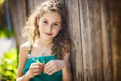 9 anos felizes da menina idosa na flor do sopro do verão Imagem de Stock