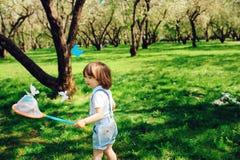 3 anos felizes das borboletas de travamento do menino idoso da criança com rede na caminhada no jardim ou no parque ensolarado Foto de Stock Royalty Free