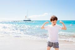7 anos felizes do menino no gesto do sucesso da vitória na praia Imagens de Stock Royalty Free