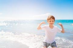 7 anos felizes do menino no gesto do sucesso da vitória na praia Fotografia de Stock