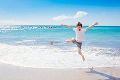 7 anos felizes do menino que salta na praia Foto de Stock Royalty Free