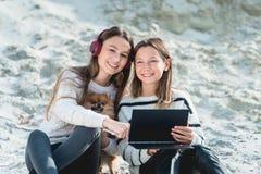 14 anos nos fones de ouvido sem fio que escutam uma música que senta-se em uma praia Fim acima uma outra menina tem um caderno ne foto de stock royalty free
