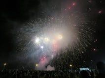Anos novos da explosão dos fogos-de-artifício no ar como a exposição do relógio dos povos em Fotografia de Stock Royalty Free