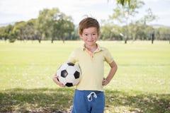 Anos novos do futebol de jogo feliz de apreciação velho do futebol da criança 7 ou 8 no campo do parque da cidade da grama que le Fotos de Stock Royalty Free