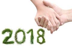 2018 anos novos Dois mil dezoito Guardar das mãos do homem e da mulher Amizade e amor Os números são feitos de ramos de pinheiro Fotos de Stock Royalty Free
