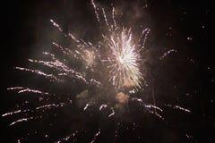 Anos novos dos fogos de artifício da véspera, diversos foguetes que explodem coloridamente com muitas faíscas no céu noturno boni foto de stock