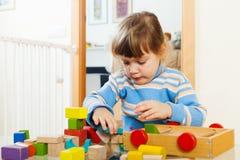 3 anos pensativos da criança que joga com brinquedos de madeira Foto de Stock