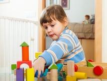 3 anos sérios da criança que joga com brinquedos Imagens de Stock