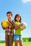 6 anos velho, menino e menina com bolas Fotografia de Stock
