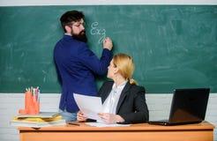 Anote su tarea Compruebe la preparaci?n Profesores que trabajan en pares la sala de clase de la escuela Educador de la escuela y  imagenes de archivo