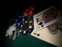 Another Blackjack. Red, blue, white, black poker chips on a green felt gaming table. Two cards and chips are spotlighted.  Jack of Spades and Ace of Spades gives Royalty Free Stock Photos