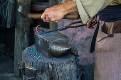 Another Blacksmith working iron. Close-up of blacksmith`s hands hammering iron Royalty Free Stock Image