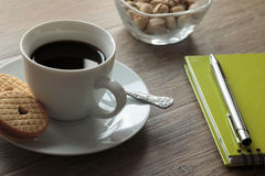 Another coffee break. Coffee in white cup with white saucer surrounded by a notebook with a pen and a bowl of pistachio Stock Image