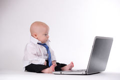 Another Day at the Office. Baby boy working on a laptop with glasses Stock Photo