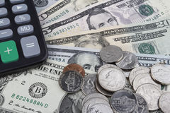 Another day at the office (USD coins and banknotes). US Dollar (USD) banknotes and coins, with a calculator in the left top corner Royalty Free Stock Image