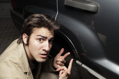 Another dent. Man expressing discontent due to his vehicles condition Royalty Free Stock Photo