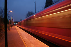 Another fast train. Fast train passing through a station at dusk Stock Images