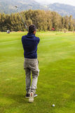 Another golf shot. A golf player making a swing on a vibrant beautiful golf course Royalty Free Stock Photography