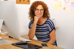 Another happy day at the office. Successful middle aged woman at her office Stock Image