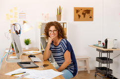 Another happy day at the office. Successful middle aged woman at her office Royalty Free Stock Photos