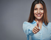 Another job well done. Confident young businesswoman giving the thumbs up against a gray background royalty free stock images