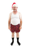 Another Lousy Christmas. Unhappy, scruffy looking middle-aged man in his underwear, wearing a Santa hat for Christmas and looking upset. Isolated on white royalty free stock photos