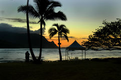 Another Lovely Sunset. Another beautiful sunset on Kauai, Hawaii.  message tent and hamock are silhouetted as well as romantic couple.  Orange and blue sunet Stock Photo