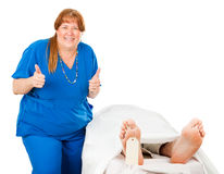 Another One Bites the Dust. Humorous photo of a nurse giving a thumbs up sign after killing off a patient.  Isolated on white Stock Photos