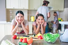 Another picture of girls leaning to table with theor hands. They look and pose on camera. Boys are wokring behind them stock photography