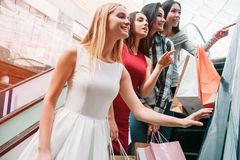 Another picture of girls standing on stairs. They are looking right and smiling. Some of them has shopping bags in their. Hands stock photos