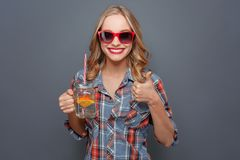 Another picture of happy person that holds a cup with juice and a piece of orange. She is showing her big thumb up. Also. Girl wears dark glasses with red edge stock photos