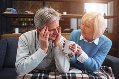 Another picture of senior couple. Close up. Man has a headache. His wife is suggesting him to drink a cup of hot tea Royalty Free Stock Images