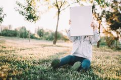 A little girl on the grass. Another picture of a small kid sitting on grass and holding a tablet in front of her face. She is thinking she can hide from imagine Stock Photography