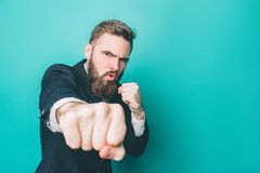 Another picture of strong guy in suite. He is showing his right fist to the camera. Thia man looks serious and brutal. Isolated on blue background Royalty Free Stock Images