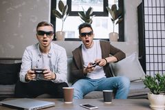 Gamers playing party. Another picture of two young gamers playing special game by using glasses for virtual reality. They are holding gamepads in their hands and Stock Photos