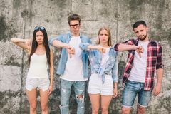 Another picture of unhappy young people standing on grey background. Some of them look a bit angry. They are showing. Thumbs down. It is dislike symbol Stock Photo