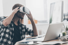 Another reality is here!. Handsome young man with long hair adjusting his virtual reality headset while sitting at his desk in creative office Stock Image