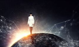 In another reality. Mixed media. Businesswoman wearng virtual reality headset walking on Earth planet. Elements of this image are furnished by NASA royalty free stock images
