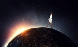 In another reality. Mixed media. Businesswoman wearng virtual reality headset walking on Earth planet. Elements of this image are furnished by NASA royalty free stock photo