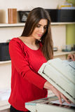 Another regular office day. Pretty young secretary using a copy machine and holding a paper at work royalty free stock photography
