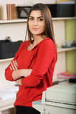 Another regular office day. Relaxed young beautiful young business woman smiling at office,arms crossed royalty free stock photo