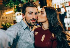 Another selfie of couple. Girl is kissing her partner while he is taking a picture. They look happy together. royalty free stock image